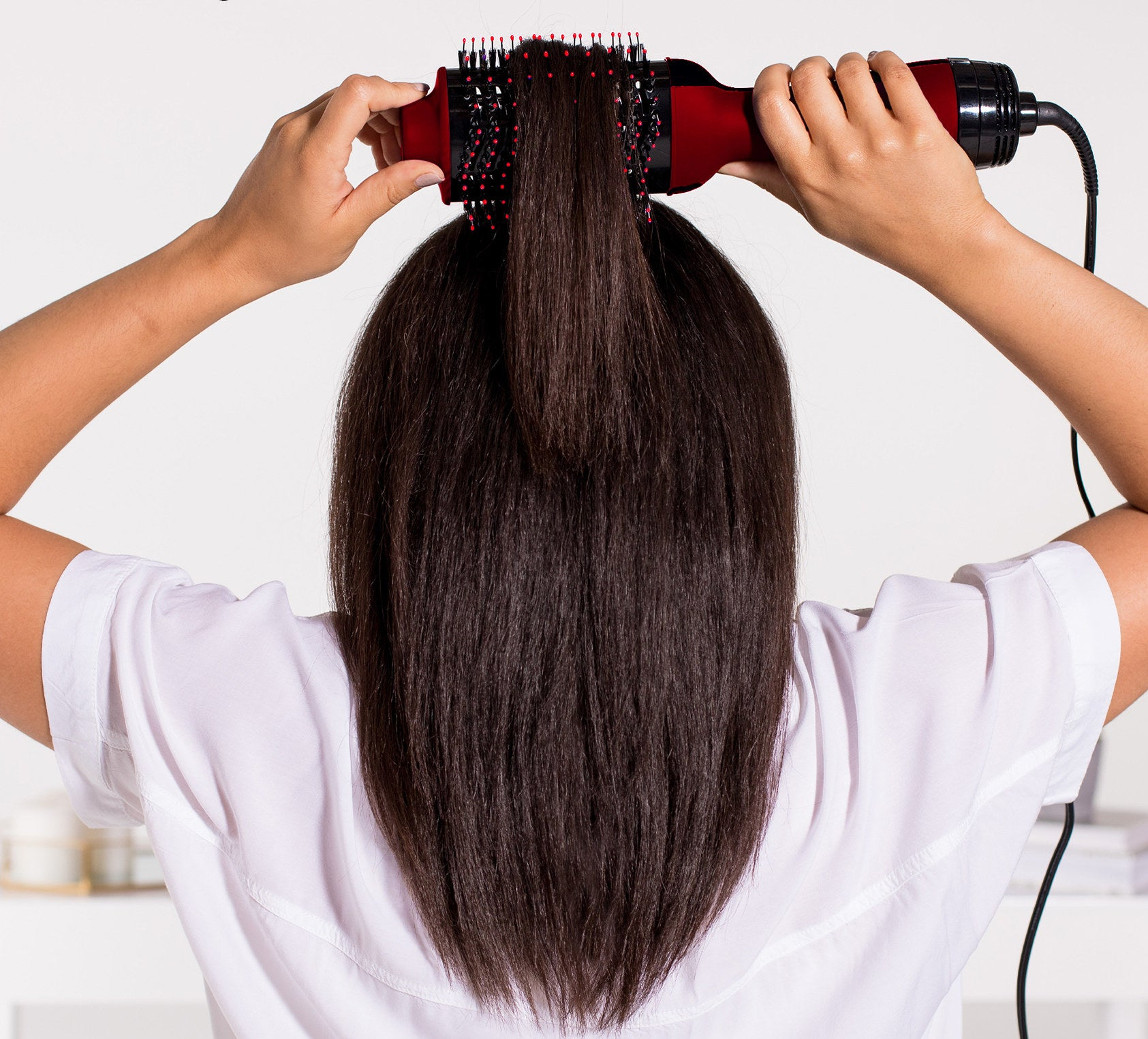 Model straightening her hair with the brush