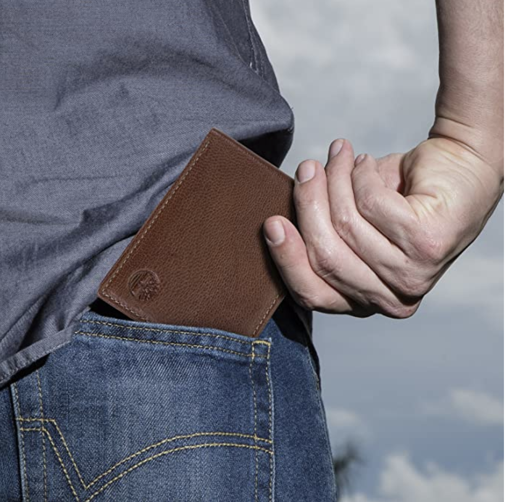 Model tucking brown wallet into back pocket of jeans