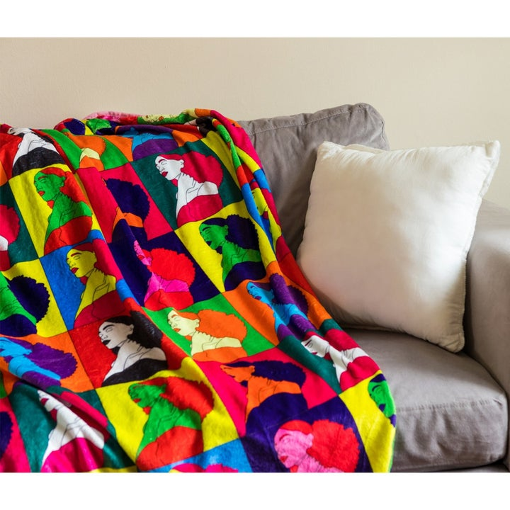 a throw blanket with bright colors and pop art portraits of a woman with big curly hair