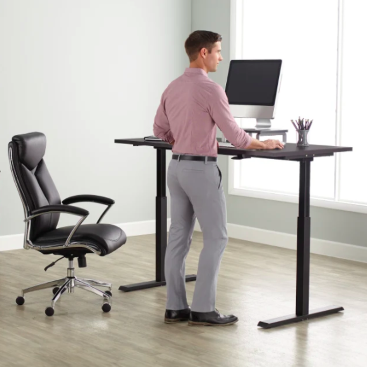 person standing at the desk with it raised to standing height