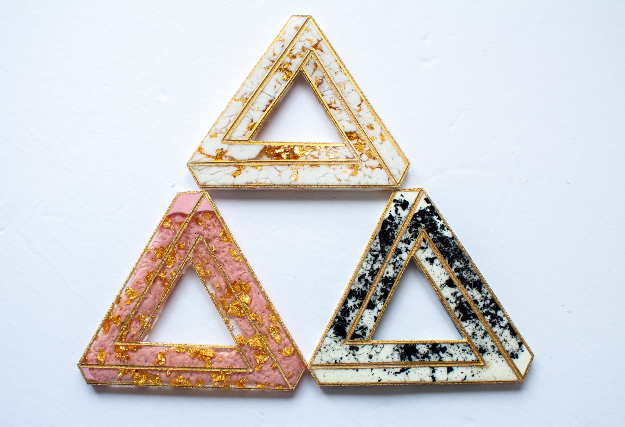 three impossible triangle shapes in pink, white, and black