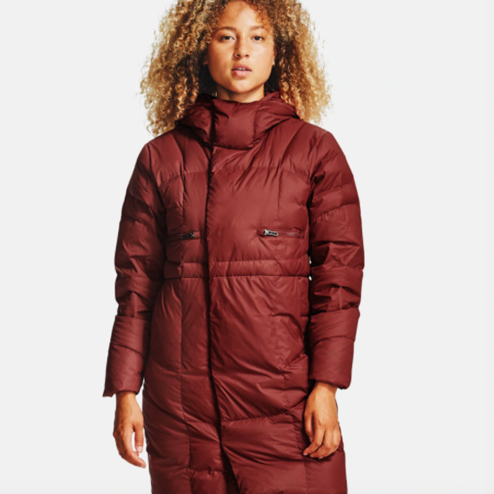 model wearing UA down parka in cinna red