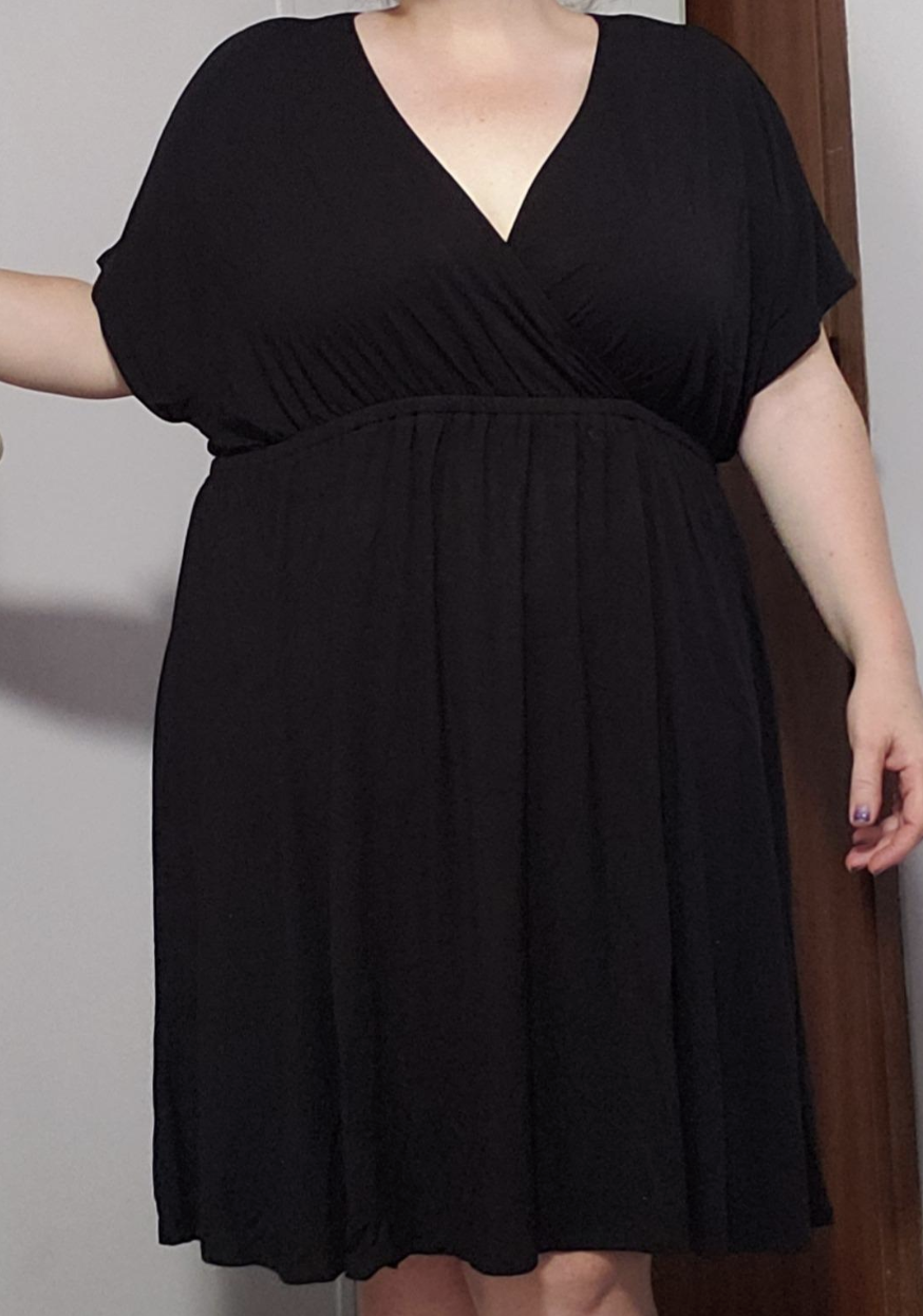 Reviewer in V-neck black dress with short billowy sleeves that cinches at waist and falls above the knee
