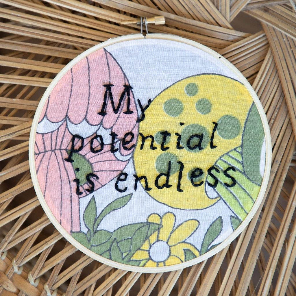 """a floral hoop with """"my potential is endless"""" embroidered in black"""