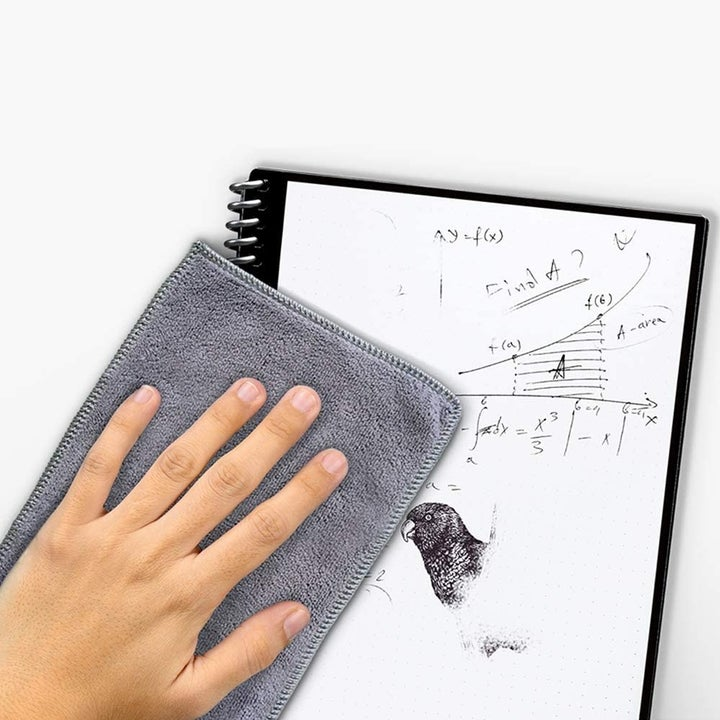 person wiping the notebook page clean with a cloth