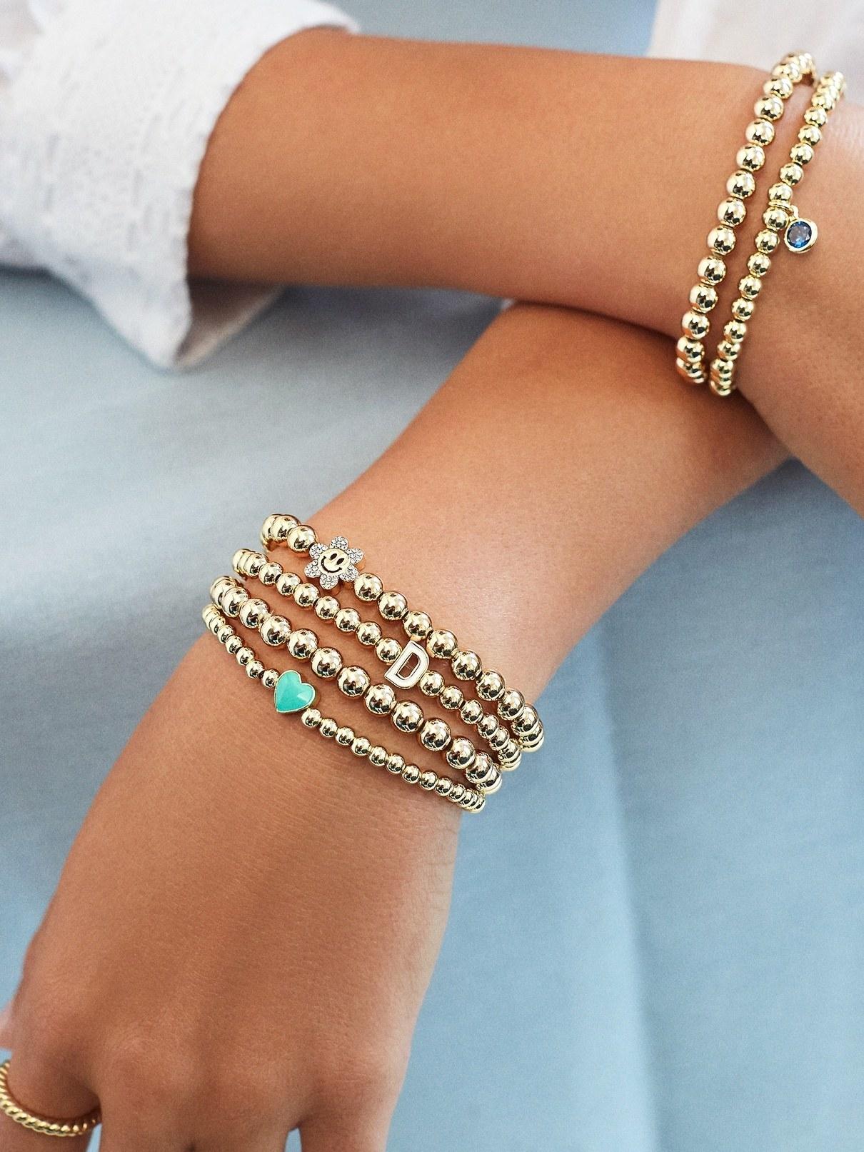 a model wearing an array of gold beaded bracelets