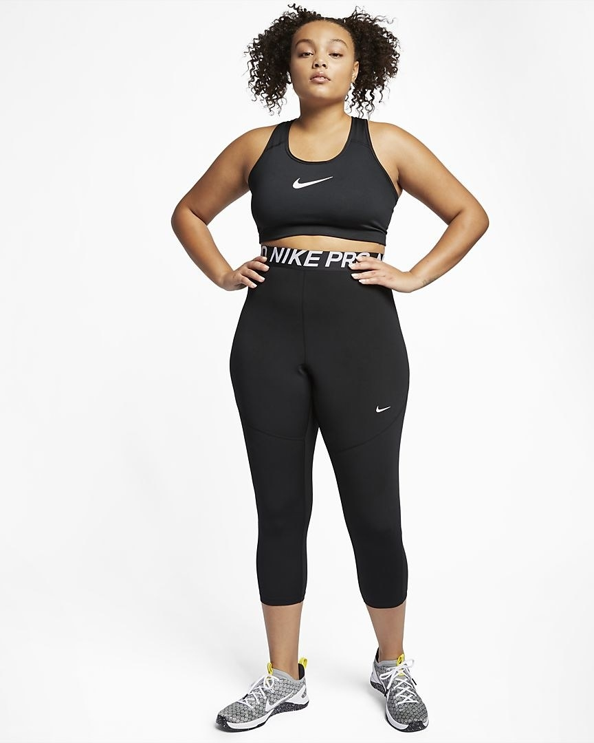 Model wearing the high-waisted mid-calf length leggings in black with a waistband that has Nike Pro written around it and a small white swoosh on the mid left leg