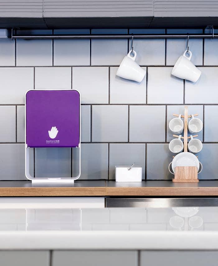 a purple cube-like hand sanitizer dispenser