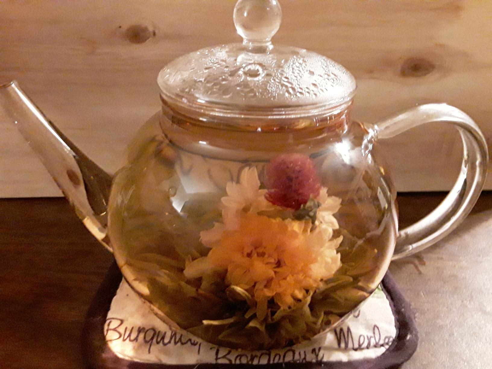 clear teapot with blooming flowers in tea