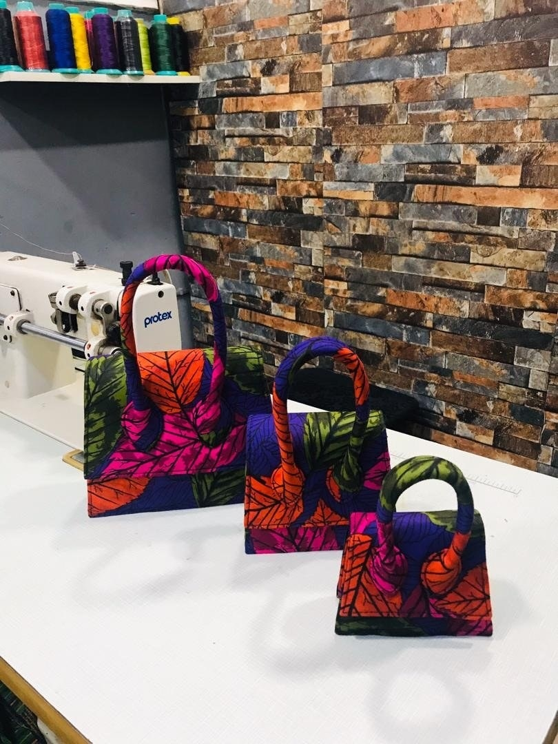 three bags in sizes graduating from small to largest with the sample floral print that's a bold orange, purple, green, and fuchsia.
