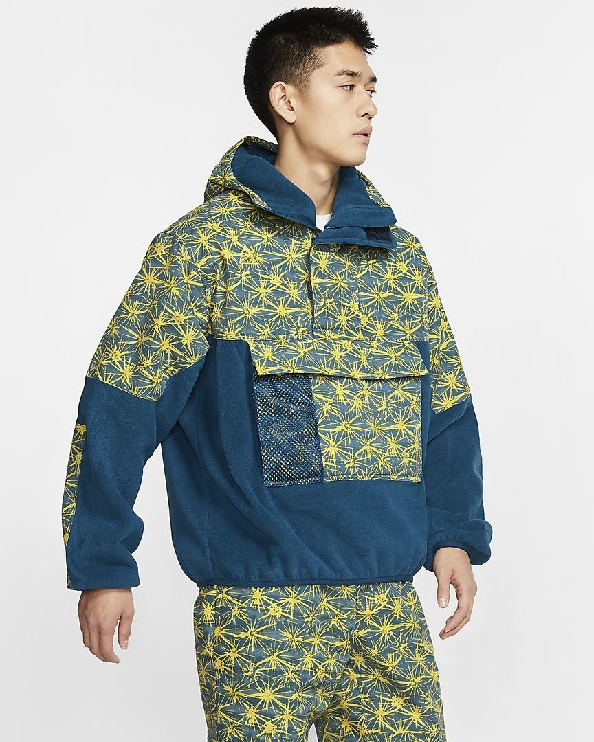 Model wearing the hooded anorak in blue with yellow star-like pattern on the top half, front pocket, and sleeves