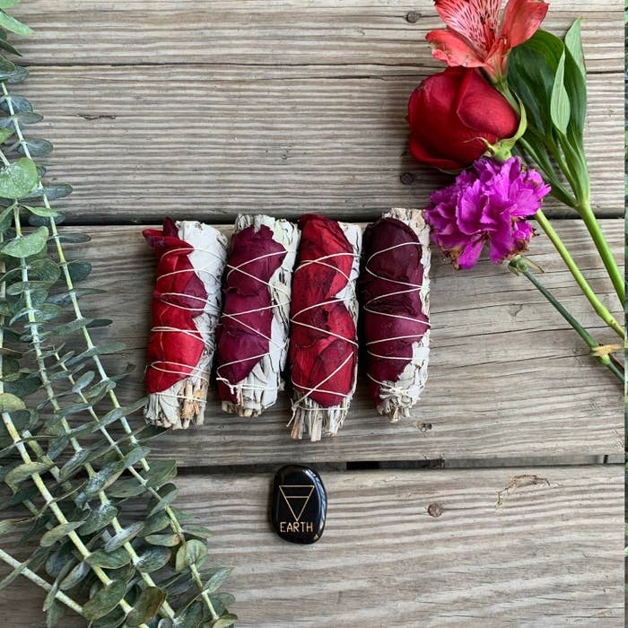 four sage smudges with rose petals wrapped around them sitting beside eucalyptus leaves