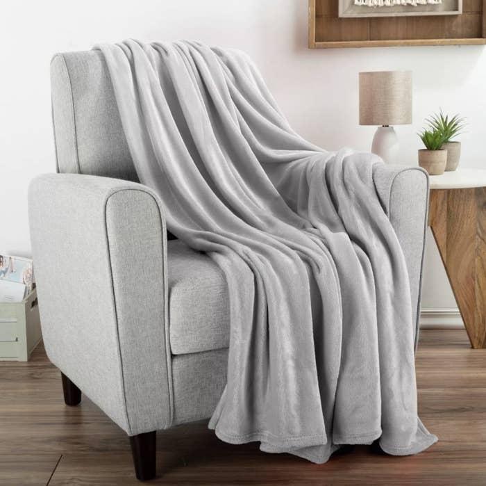 the oversized fleece throw draped over a gray chair
