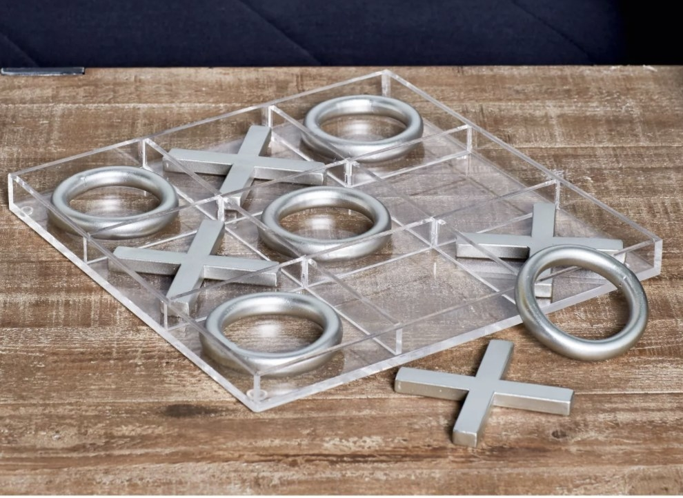 the tic tac toe set with silver pieces on top of a wood table