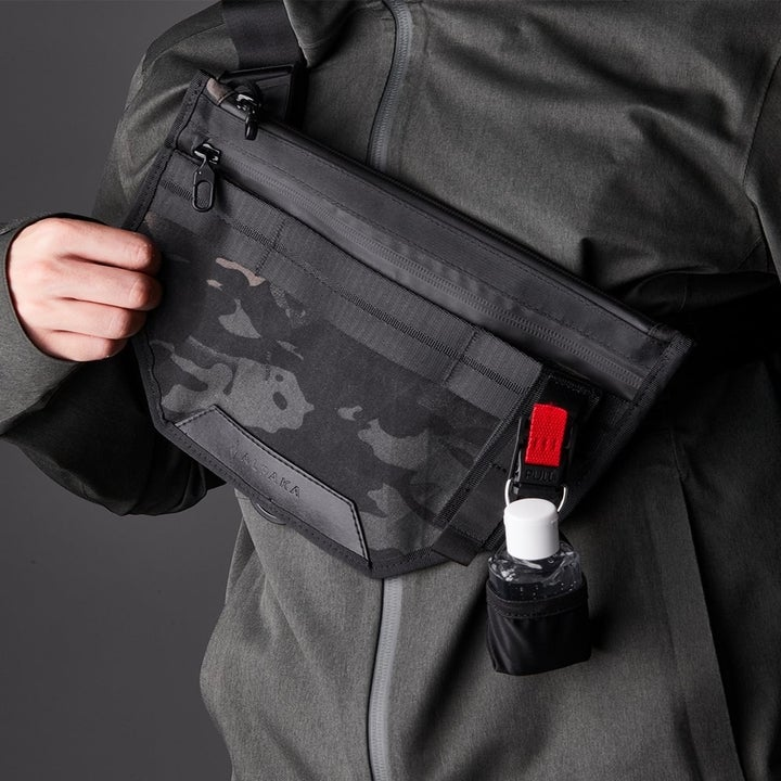 the fanny pack-style pouch pulled to the front with the smaller hand sanitizer pouch clipped onto it