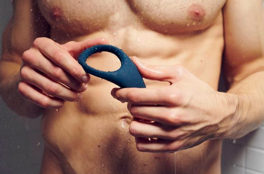 Person holding ring sex toy while in shower
