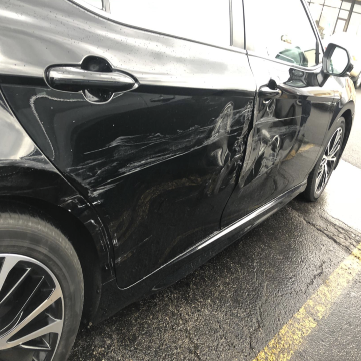 black car with dents and visible long, white scratches.