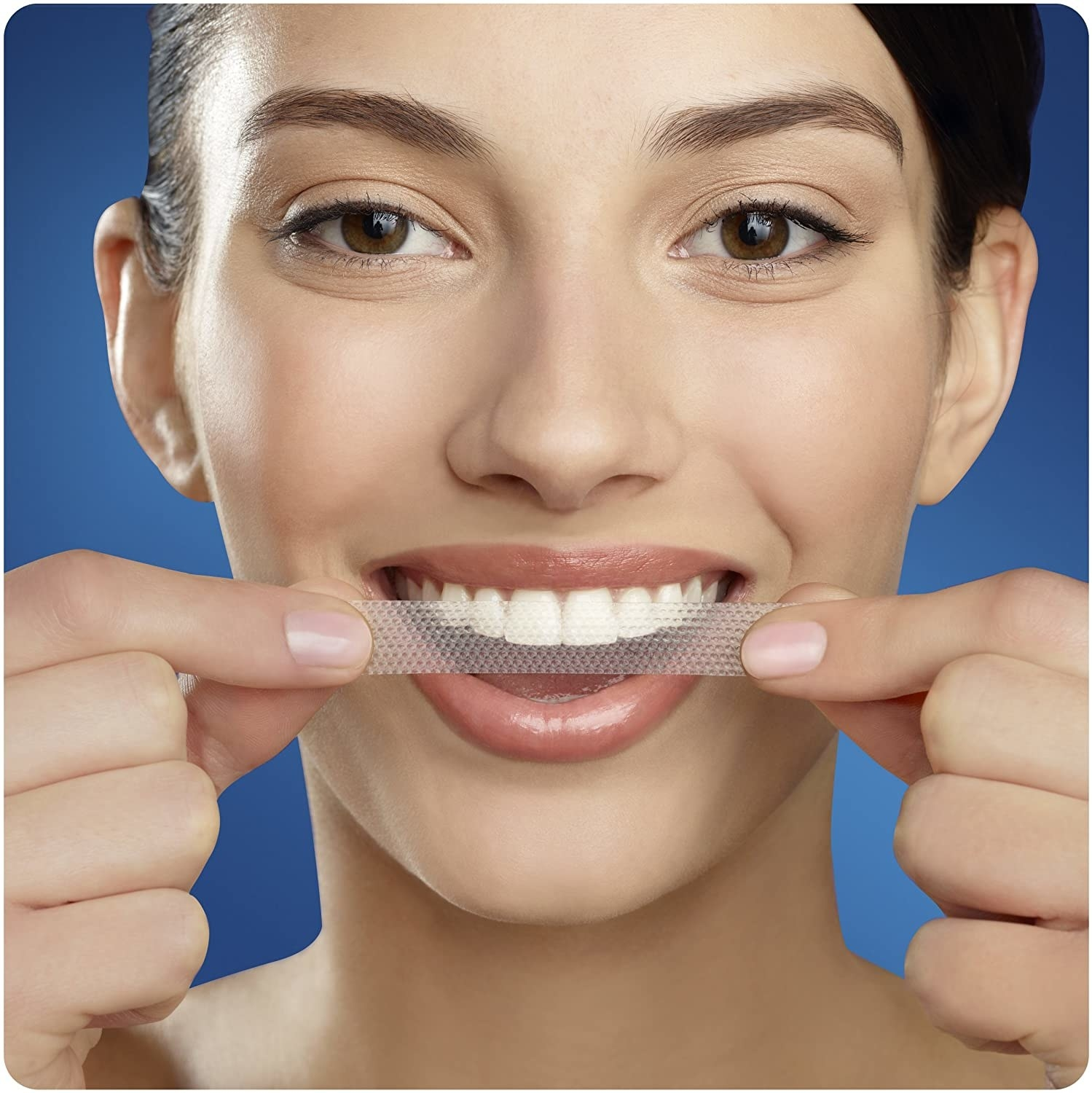 A person placing a whitening strip on their teeth