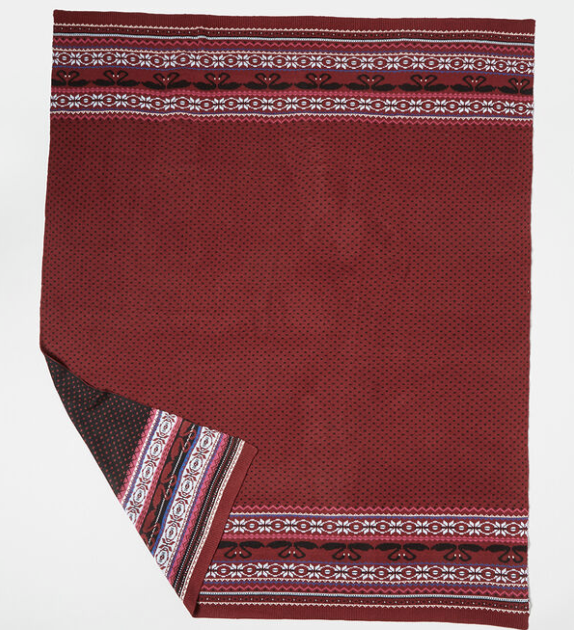 A red print blanket with black and white fair isle print at the borders