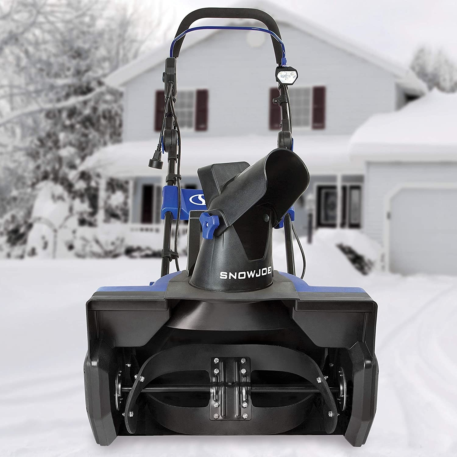 The snow blower in front of a snow-covered house