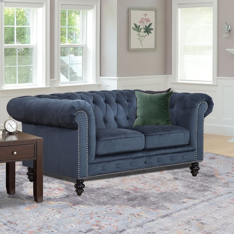 Navy tufted couch that seats two people