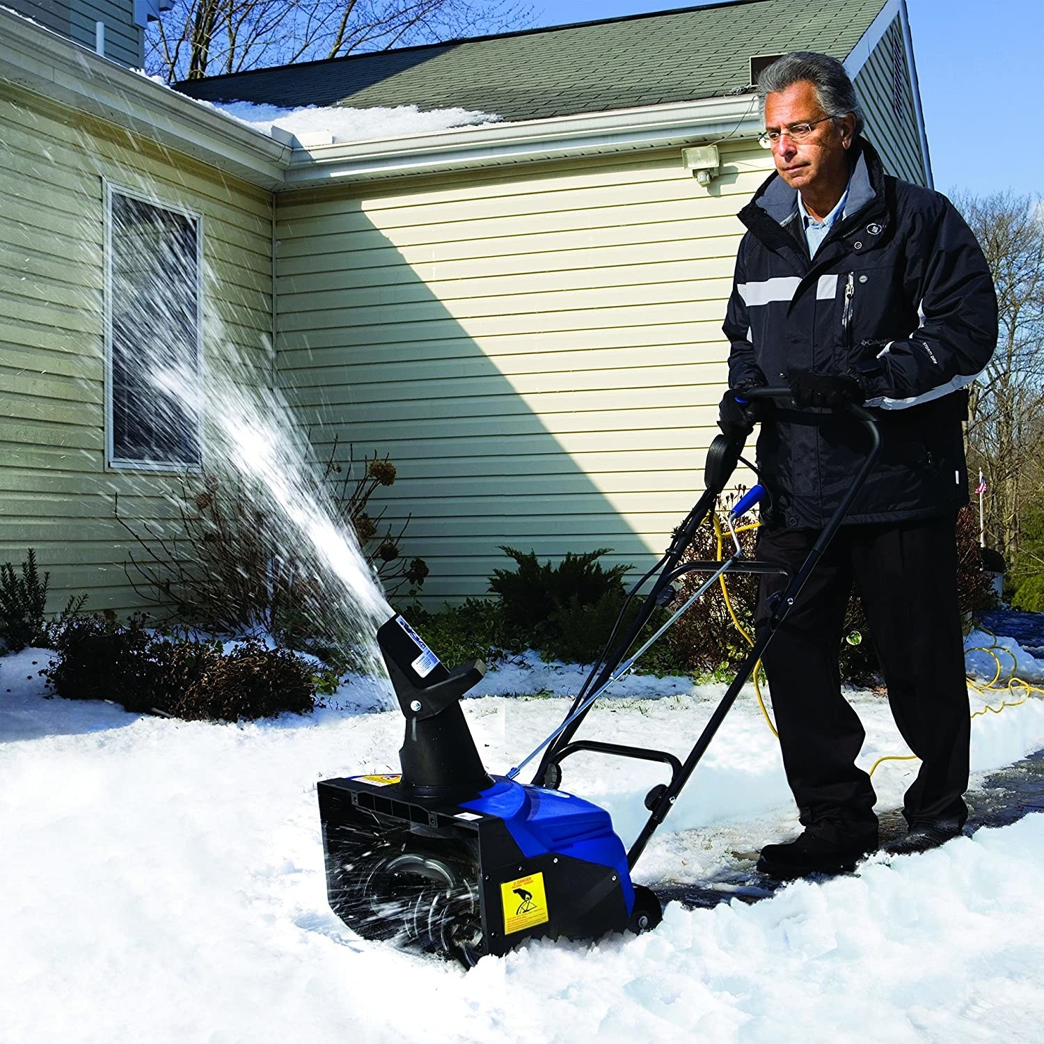 A person using the snow thrower on their lawn