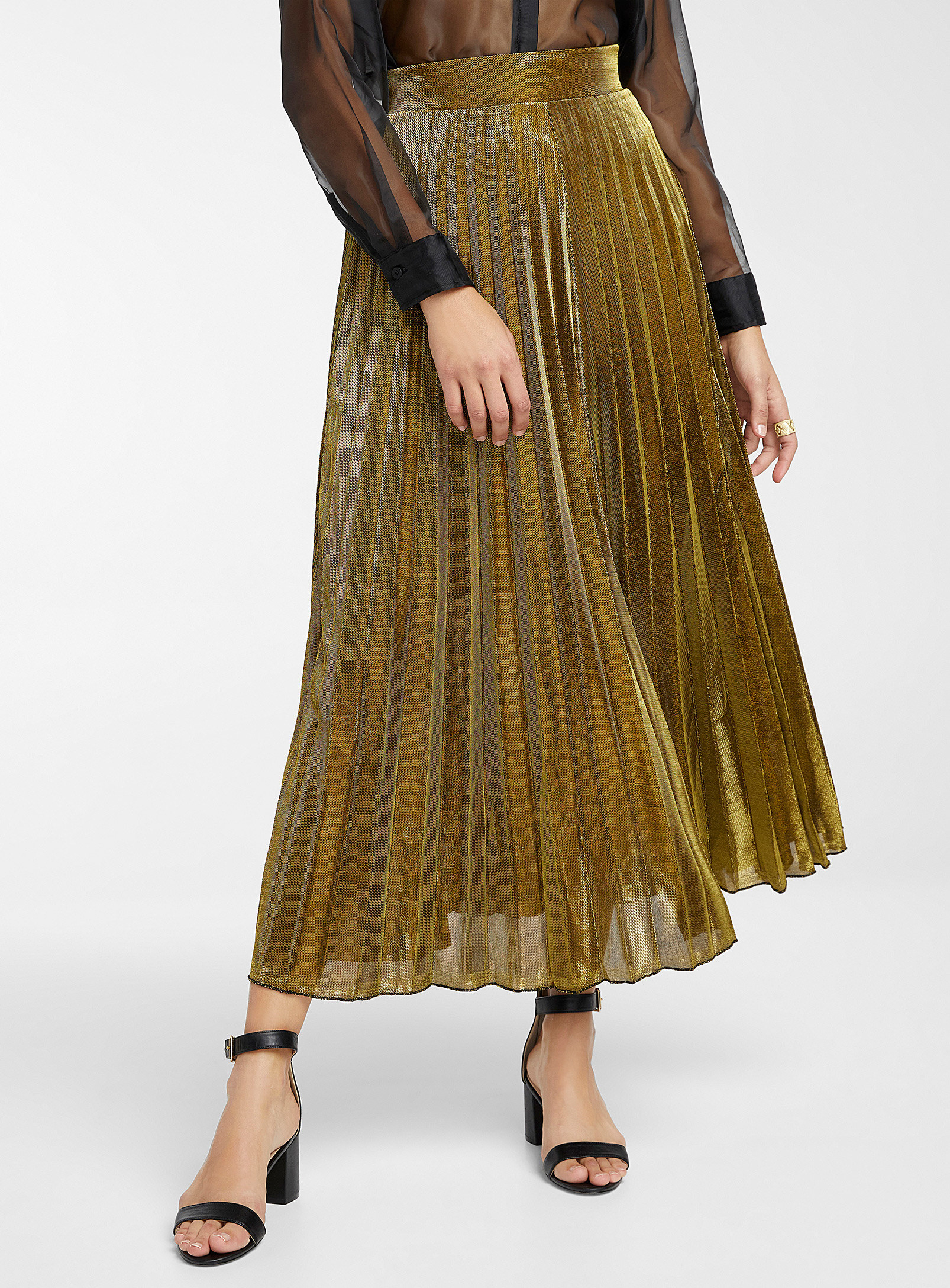 A person wearing along pleated skirt