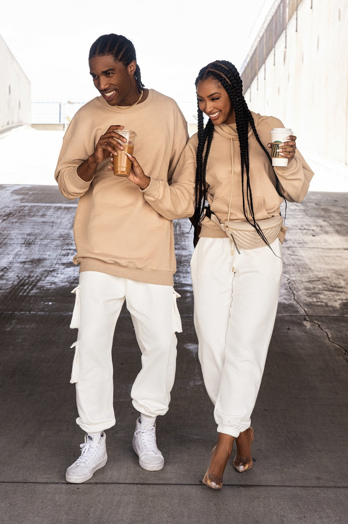 male and female model wearing the tan sweatshirts with with white joggers. The guy has on white sneakers while the woman has on clear heels. Her sweatshirt also has a fanny pack over it.