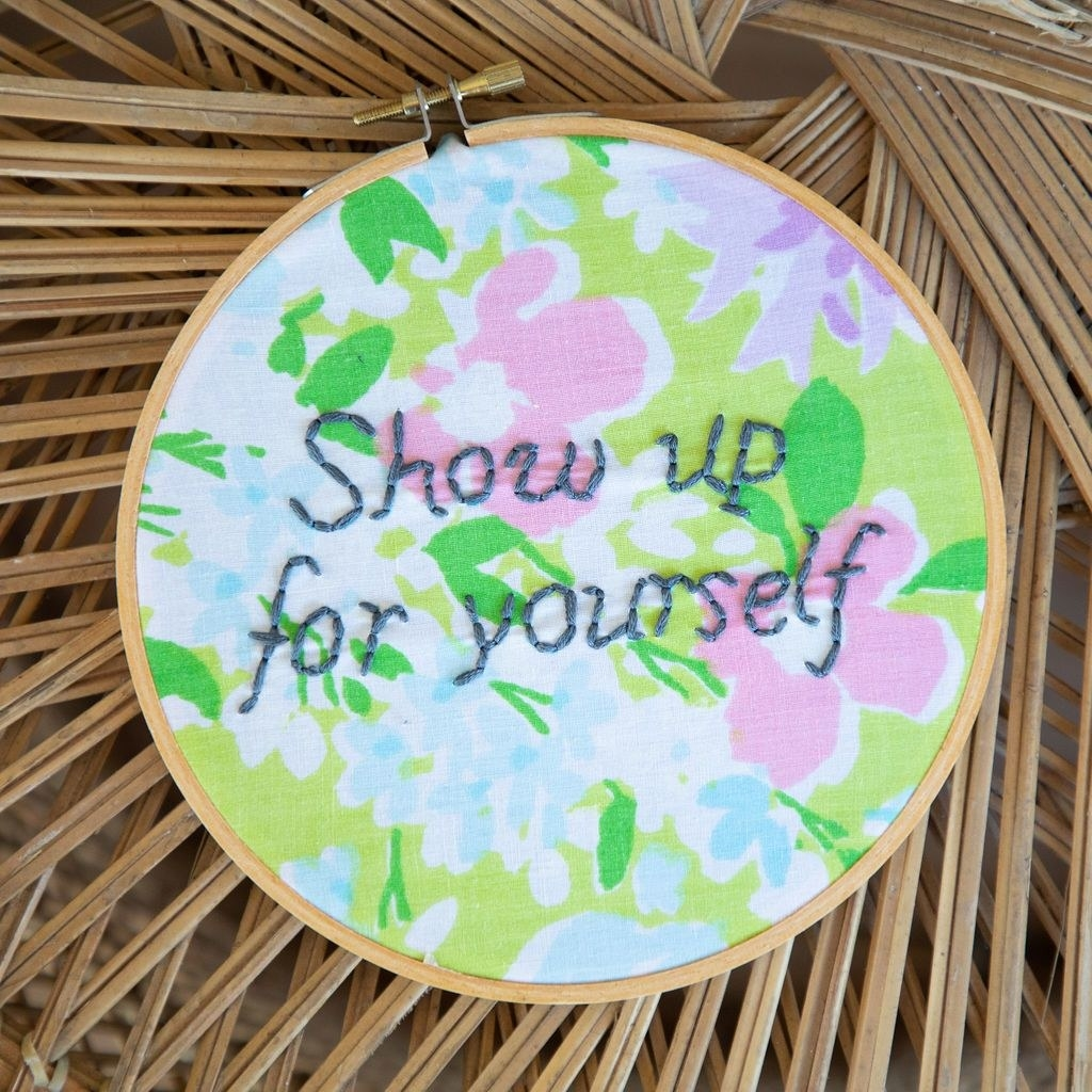 "a floral hoop with ""show up for yourself"" embroidered in grau"