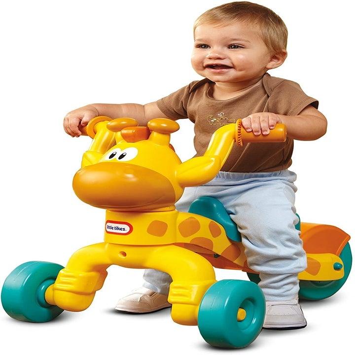 Toddler on a four wheeler shaped like a giraffe