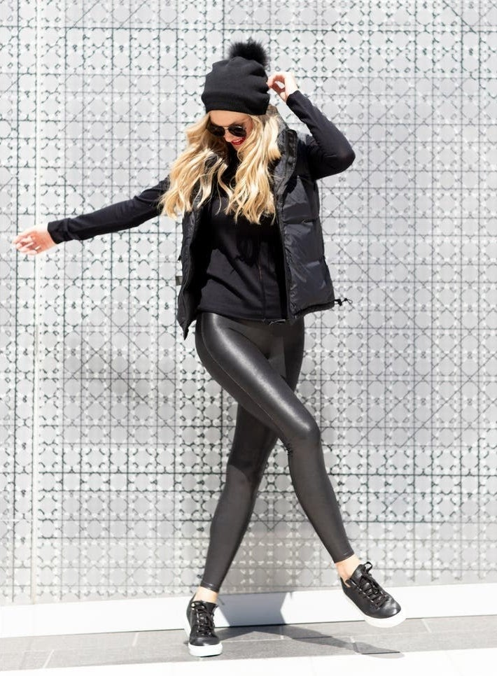Model wearing the leggings with black sneakers, a black long-sleeve, black vest, and black beanie