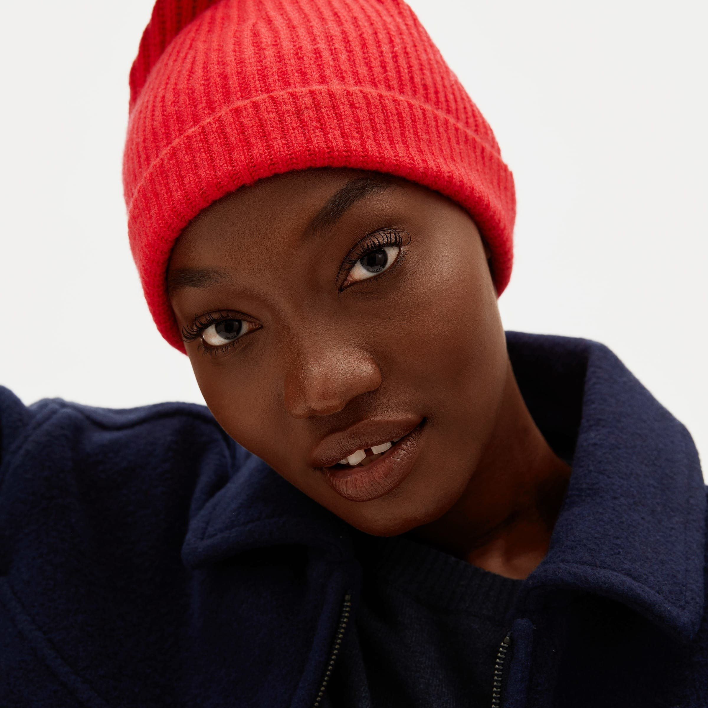 a model in a bright pink beanie