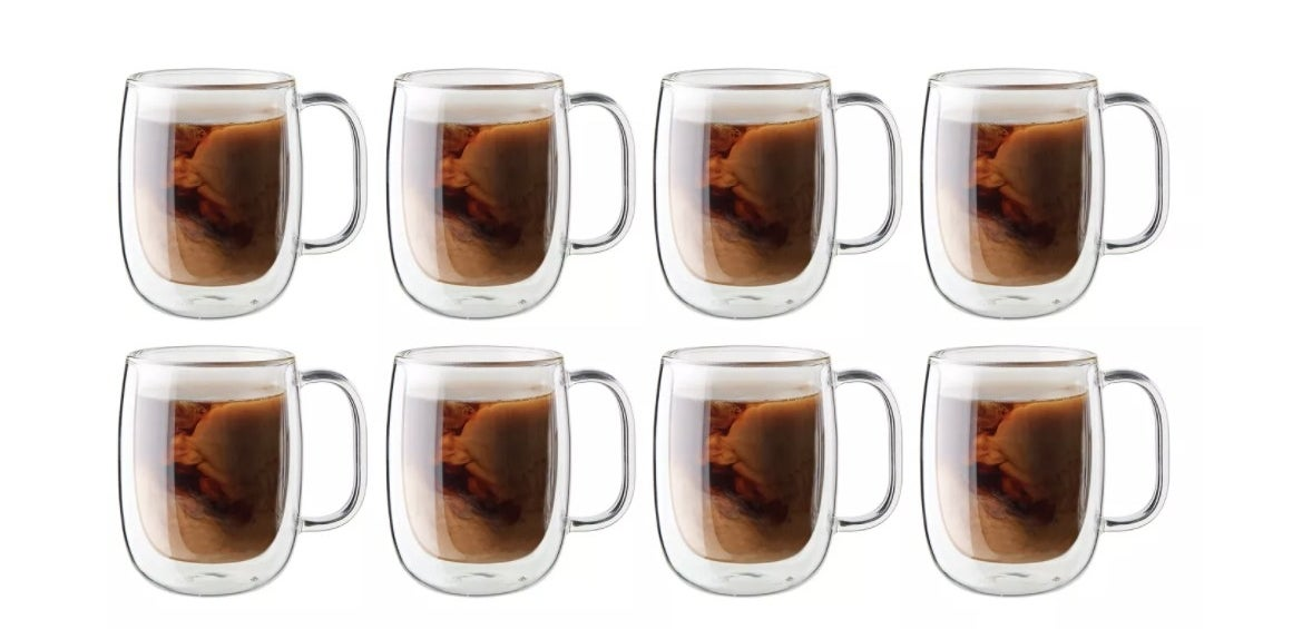 a set of 8 mugs with coffee inside of it