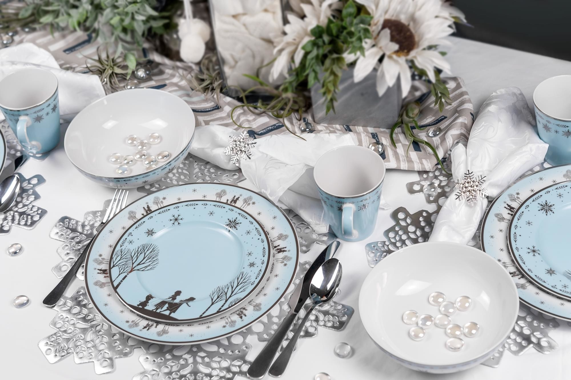 small blue plate with ana, elsa, and olaf on top of a light blue plate with the same design repeated on the edge