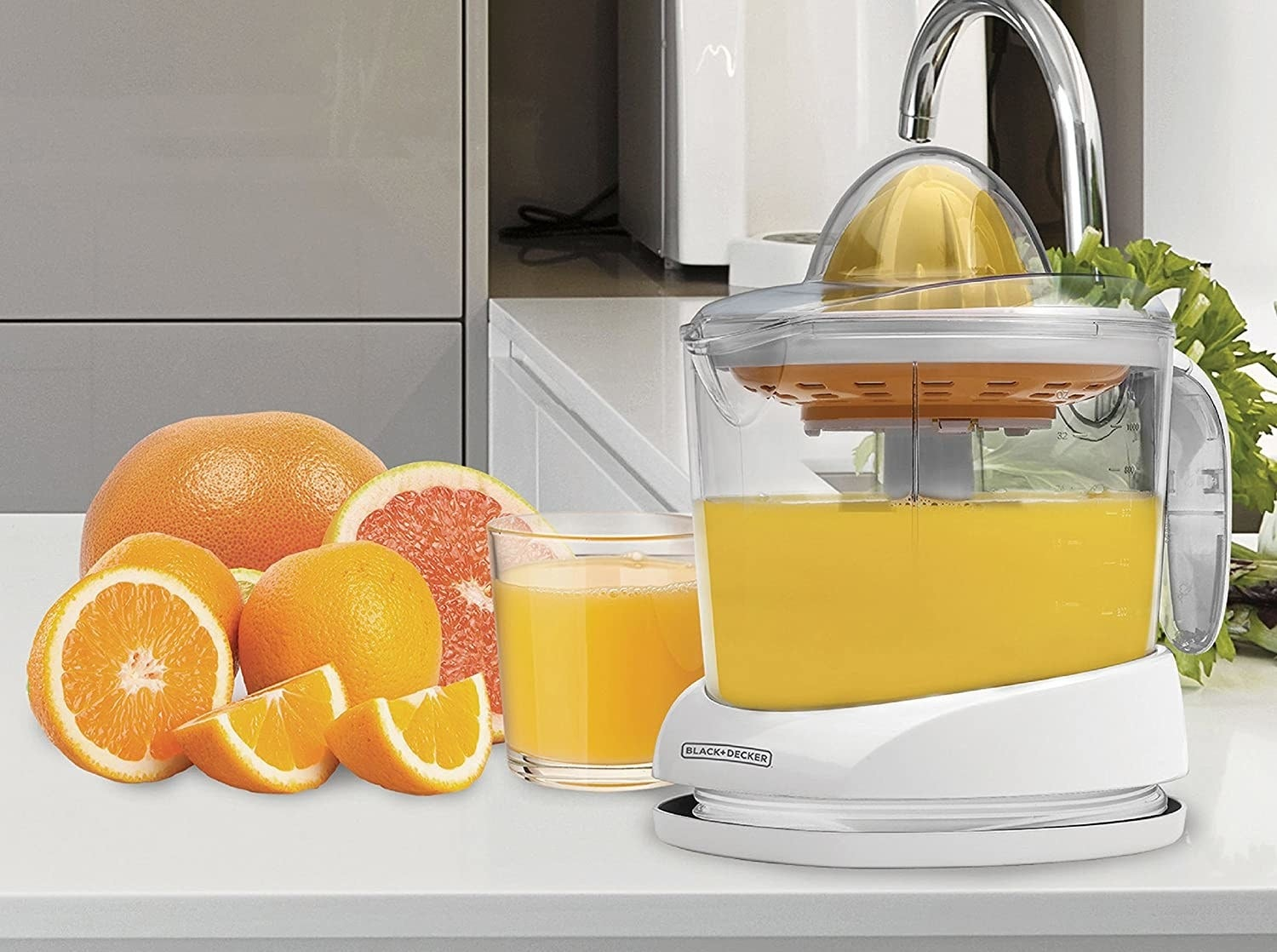 A citrus juicer surrounded by fruit on a kitchen counter