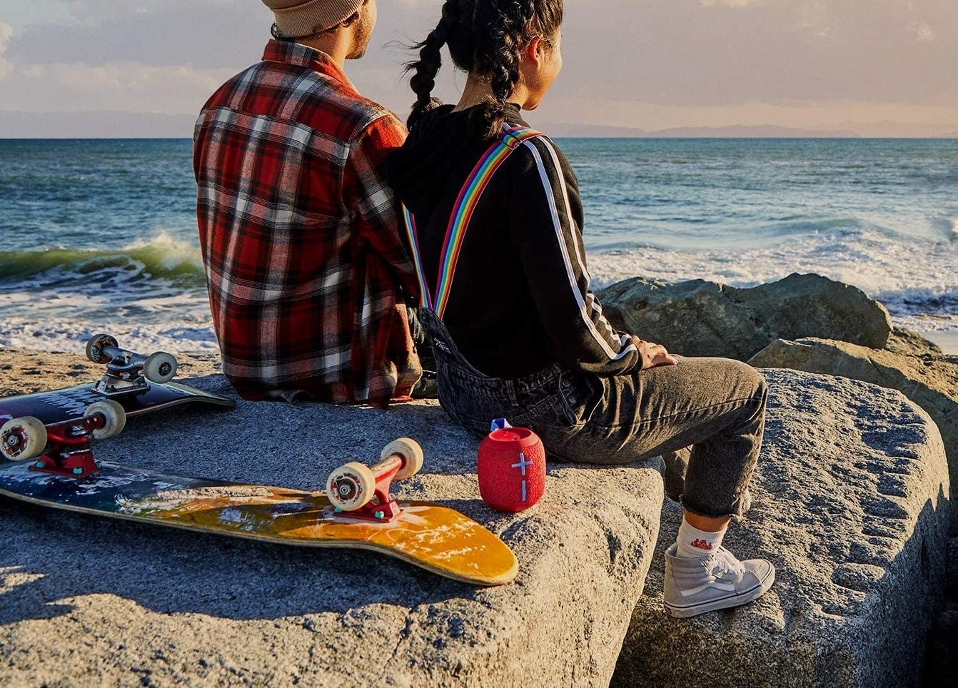 Two people sitting on rocks near a beach with a small speaker behind them
