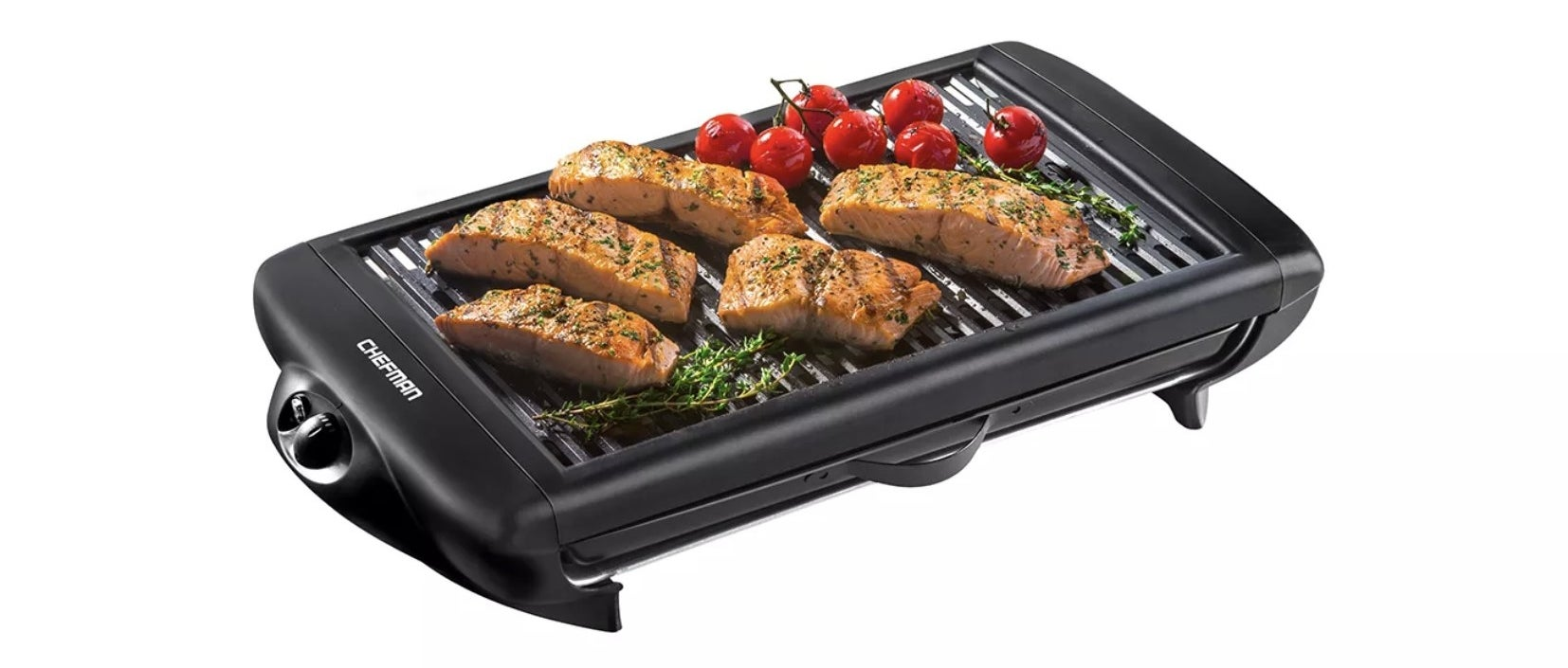 the smokeless indoor grill with salmon, tomatoes, and fresh herbs on it