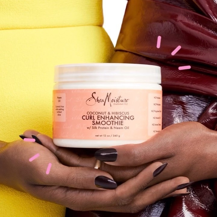 A model holding the Shea Moisture curl enhancing smoothie cream