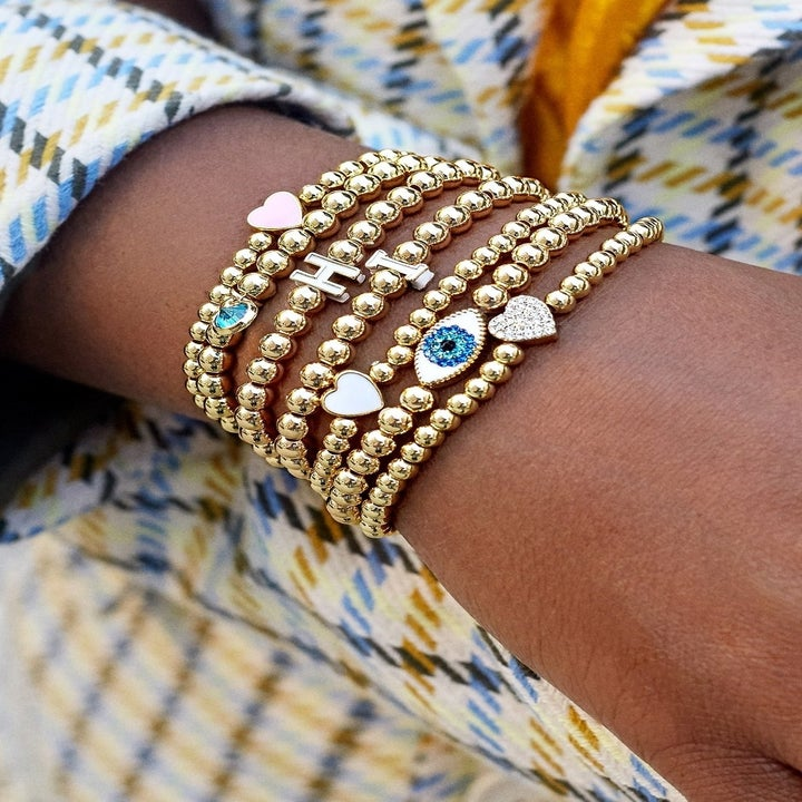 A stack of the bracelets with different charms on a wrist