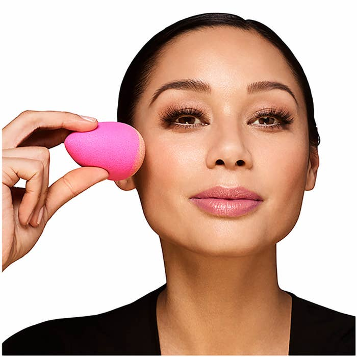 Model applying foundation with beautyblender