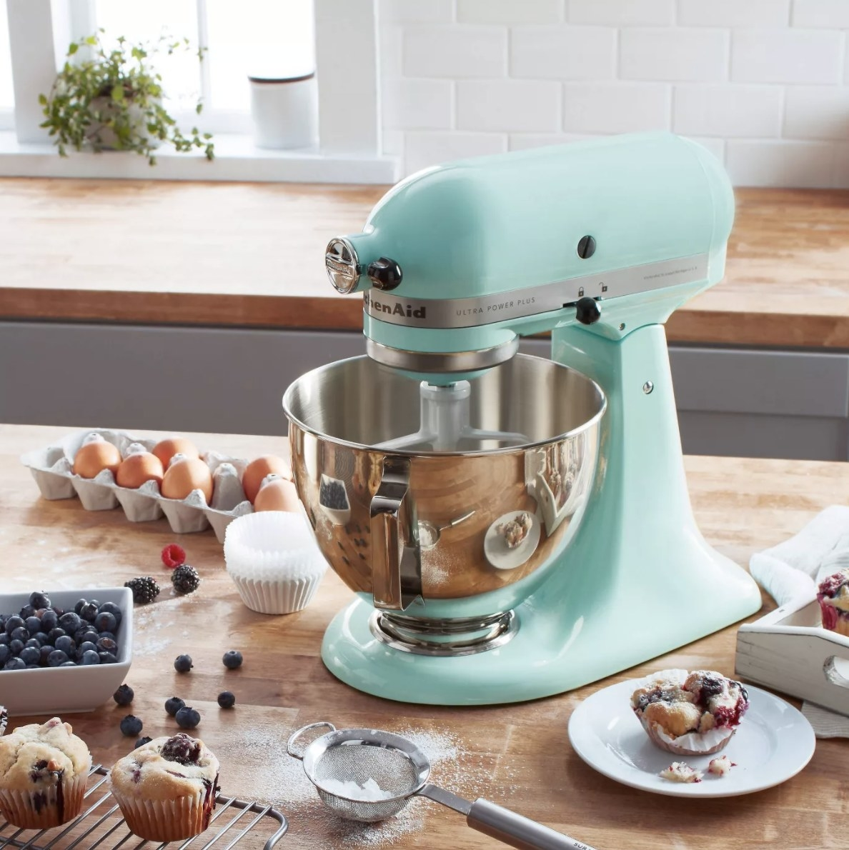 The mixer in ice blue surrounded by ingredients to make blueberry muffins and blueberry muffins