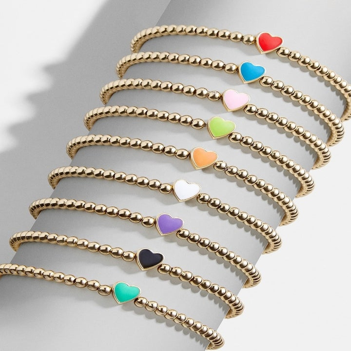 Several of the gold bead stretch bracelets each with a different color heart bead