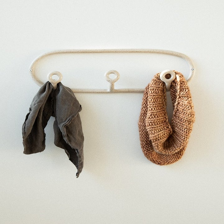 a rounded coat hanger with three hooks attached
