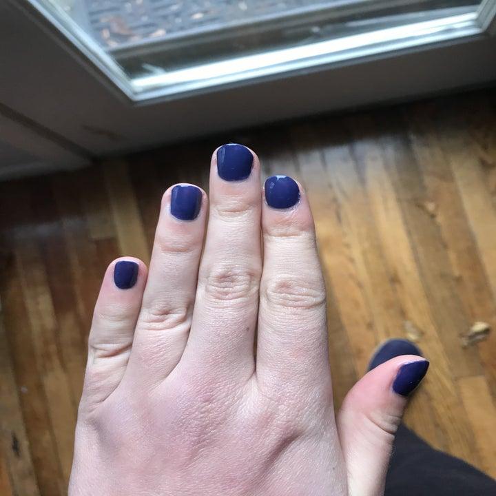 the writer's nails painted dark bluish purple