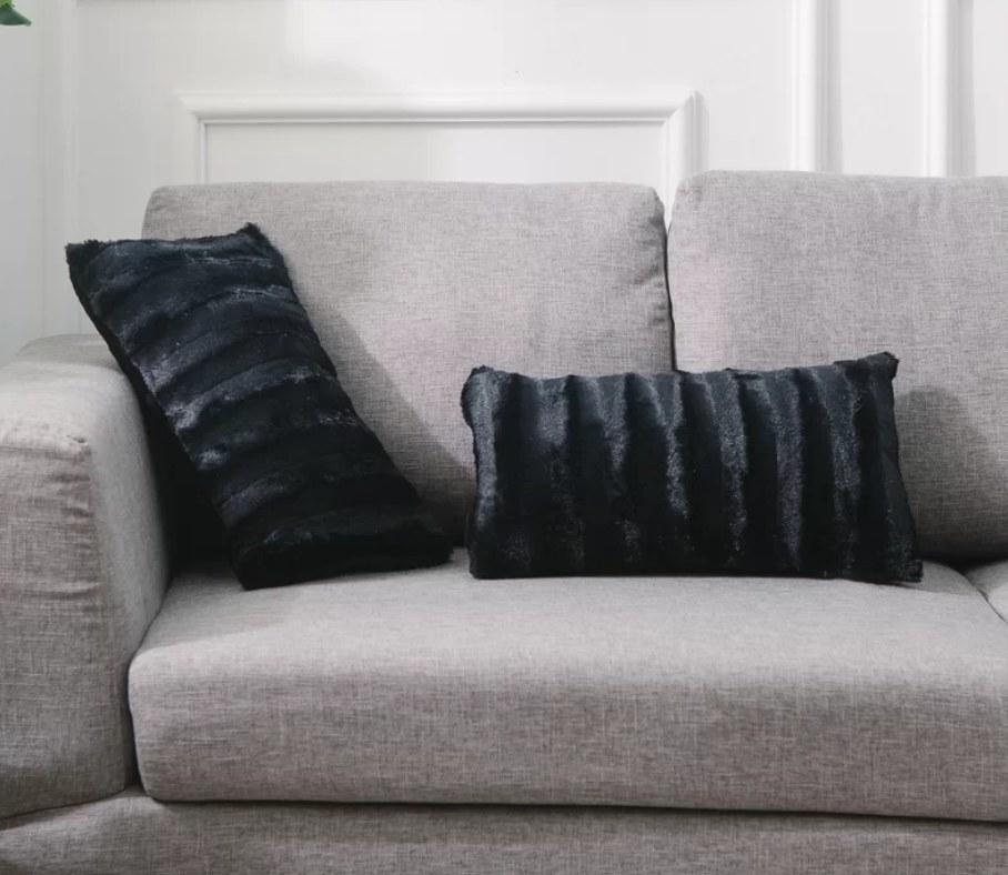 Two black faux fur decorative pillows
