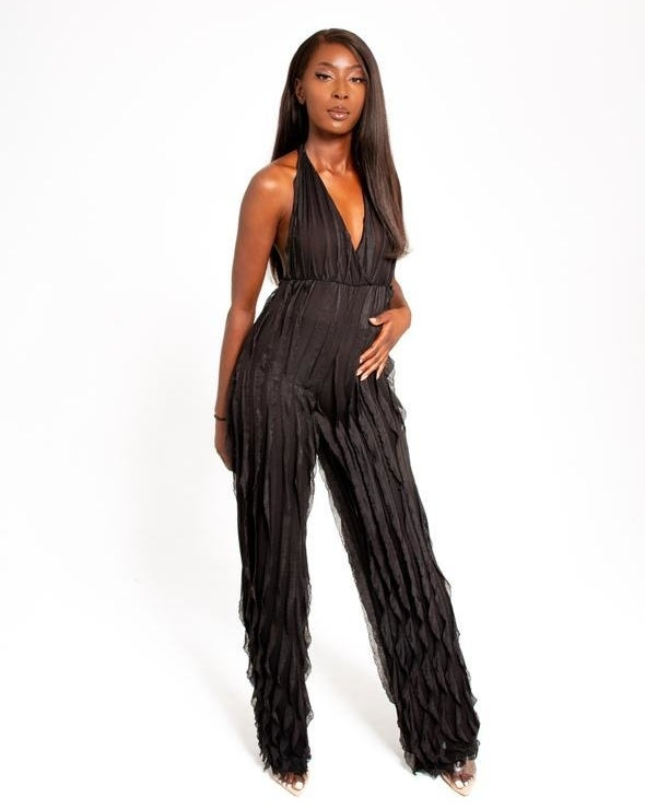 Model wearing the black V-neck sleeveless jumpsuit