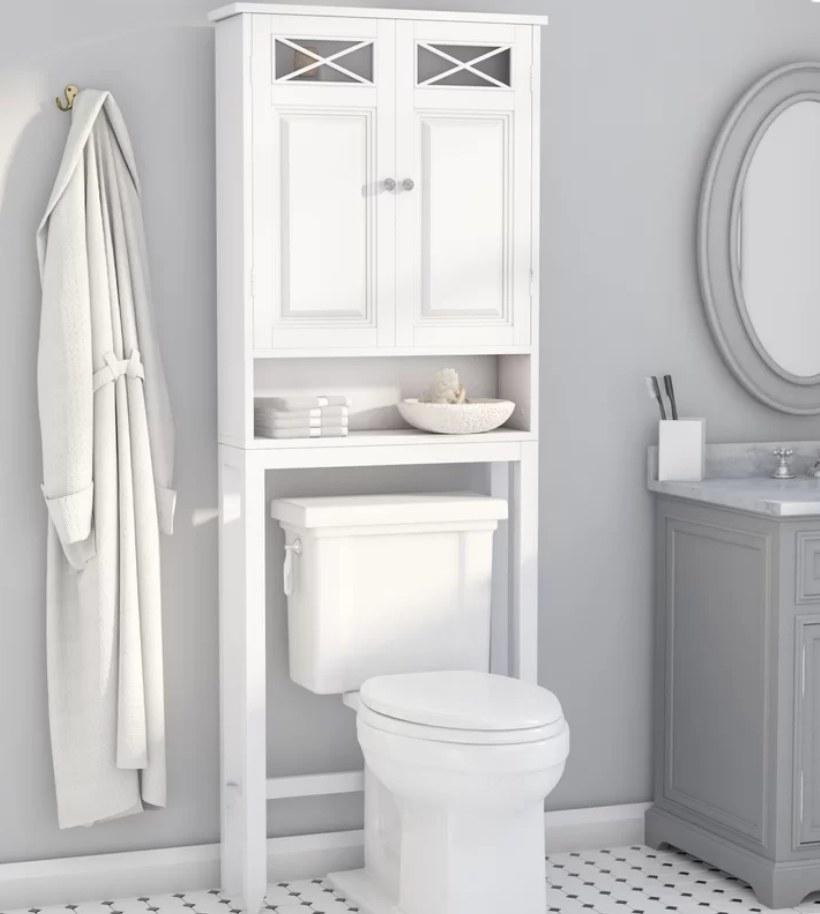 White organizer cabinet over white toilet