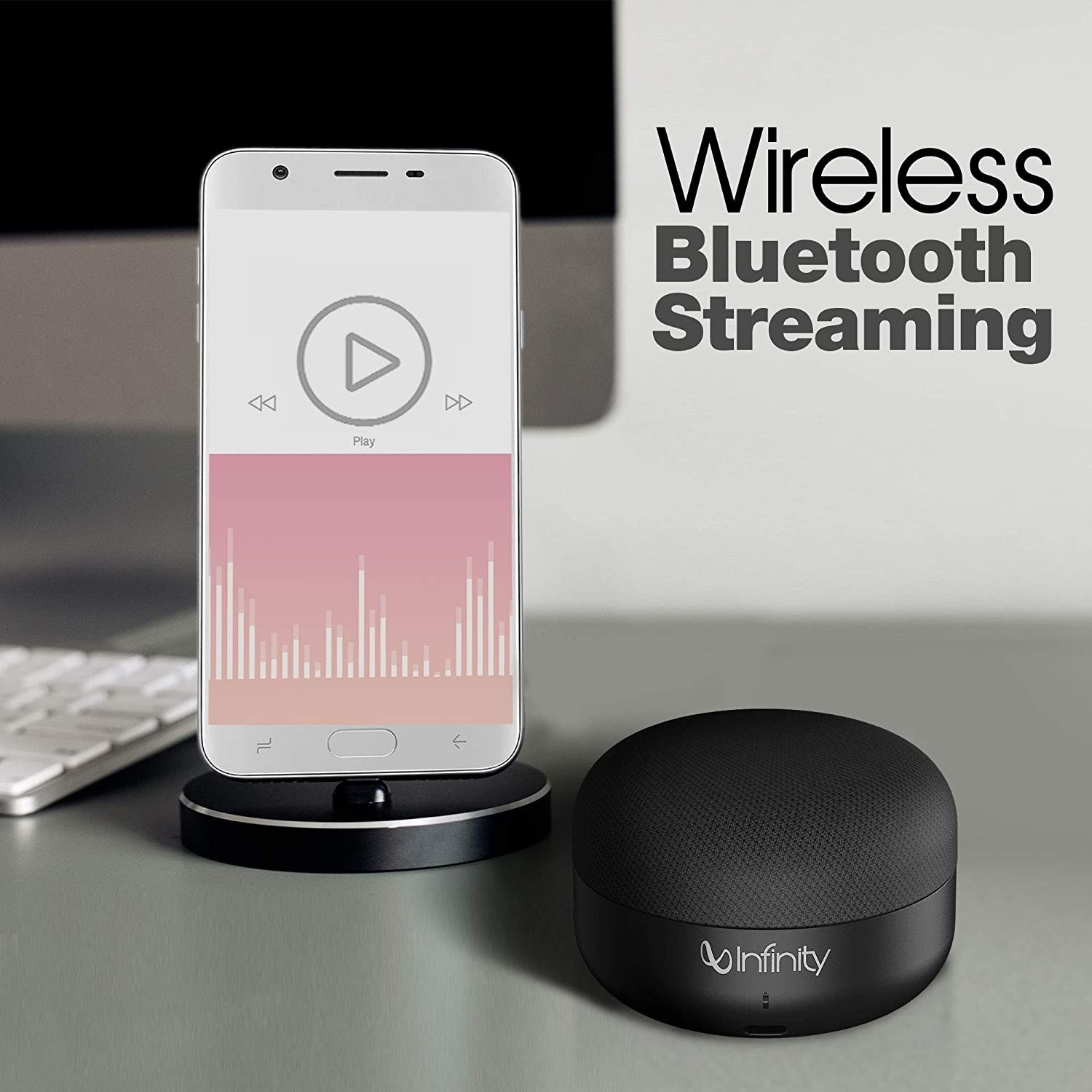 """Bluetooth speaker beside a phone, with text above it reading """"Wireless Bluetooth Streaming""""."""