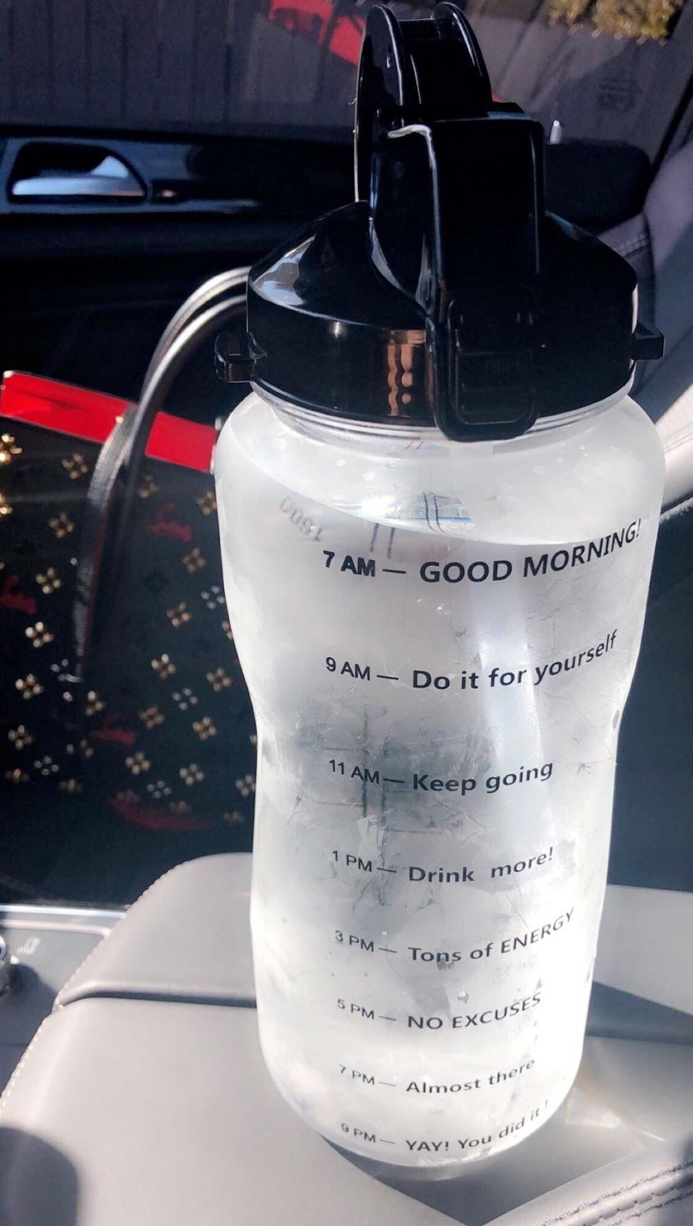 A reviewer's large clear water bottle with every two hours from 7 am to 9 pm marked with a different motivational phrase down the bottle