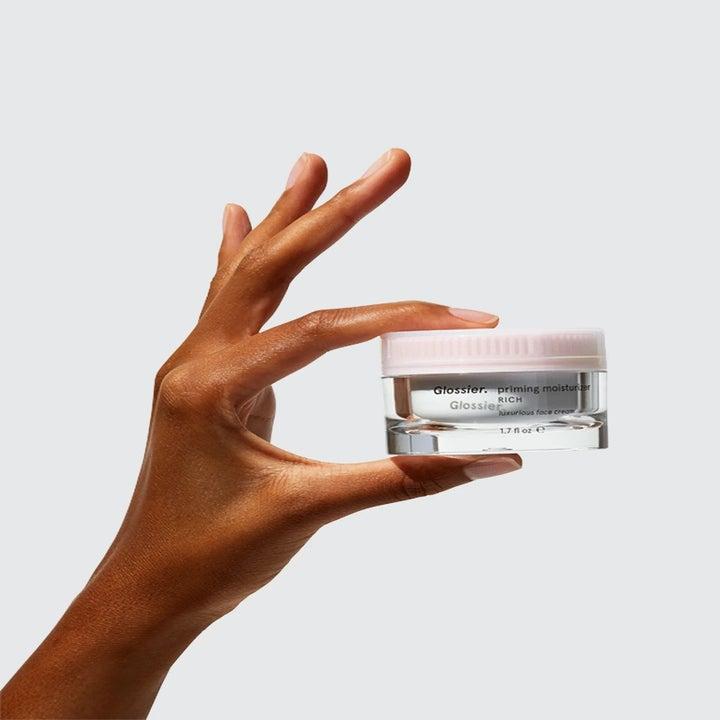 Model holds jar of Glossier Priming Moisturizer in their hand